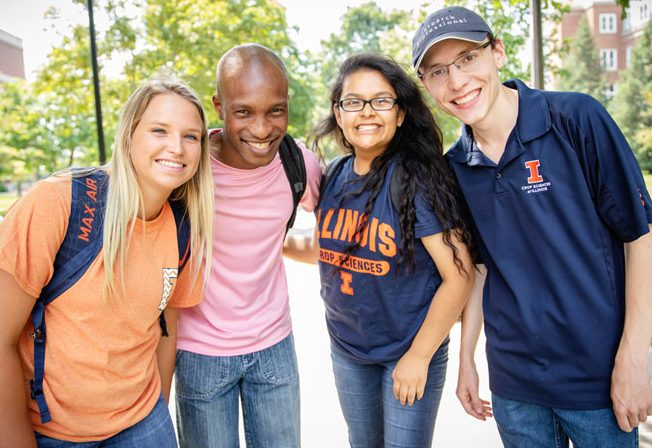 Four Illinois students smiling on a summer day.